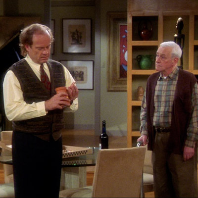 Frasier and Martin standing together. Frasier is holding the cheese filled earthenware with a critical mimic.