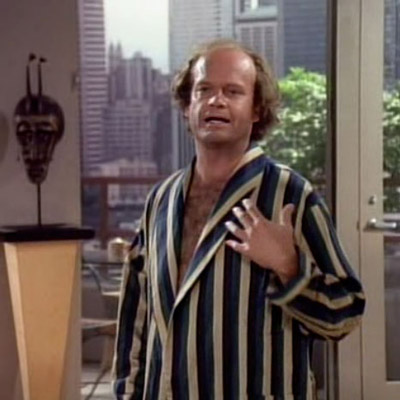 Frasier is making a sarcastic hand gesture illustrating his failing heart due to Martin's fatty breakfast.