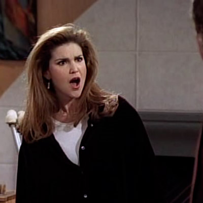 Roz is looking at Frazier, with a surprised and hateful facial expression.