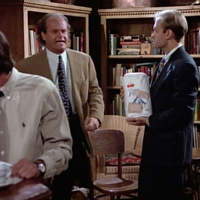 "Frasier is storming past Niles, who is standing holding his ""flour child"" inside Café Nervosa."
