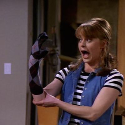 Daphne is performing a puppet show, with a sock on her hand.