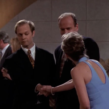Niles is making a very weird facial expression as he shakes hands with a woman at the party.
