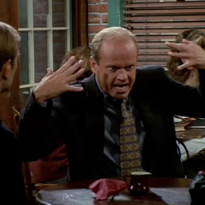 Frasier is making hand gestures and pointing his hands towards his face.