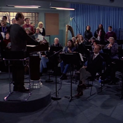 Fraiser in the position as the conductor. He is standing in front of the entire orchestra answering their questions.