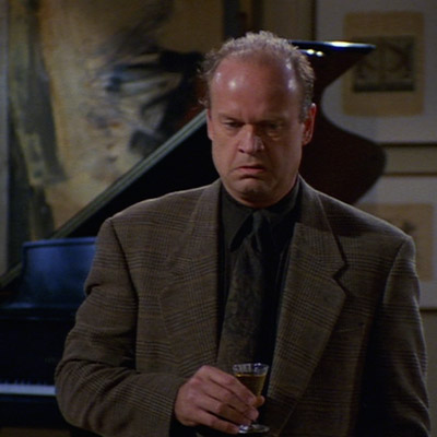 Frasier is standing with a Sherry in his hand and a resignedly expression on his face.