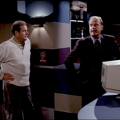 Frasier is trying to collect his lost suitcase and is standing waiting for the clerk to return to the desk.